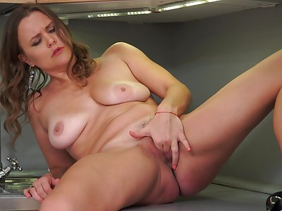 By oneself matured Goldie Glass moans while masturbating almost the kitchen