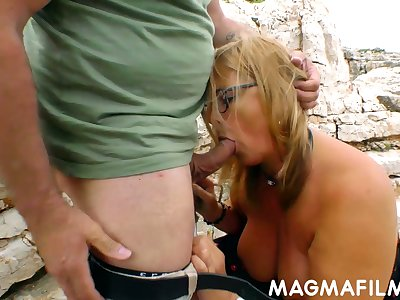 Mature couple is having dirty extreme sex on a rocky shore
